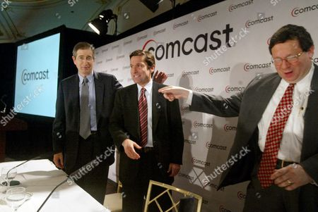 Comcast Corp. Executive Vice President David L. Cohen points to chief executive Brian Roberts, left, and Stephen Burke, head of the company's cable division, after a news conference in New York . Comcast, the nation's biggest cable systems operator, announced Wednesday that it has offered to buy Walt Disney Co, for stock valued at about $54 billion, and to assume $11.9 billion in Disney debt