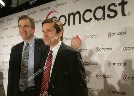 Comcast Corp. chief executive Brian Roberts, left, and Stephen Burke, head of the company's cable division, pose for photos in New York after announcing that Comcast has offered to buy Walt Disney Company. Comcast, the nation's biggest cable systems operator, has offered to buy Disney for stock valued at about $54 billion, and to assume $11.9 billion in Disney debt