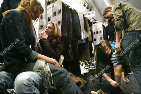 Stock Photo of Models Tatiana Kovylina, far left, and Carl Lindman, second from left, wait backstage to be outfitted while Sam Broekema, second from right, fits a shoe for model George Allan before the John Varvatos fall 2004 fashion show in New York, . Broekema was one of thirty dressers with the Stephanie J company who outfitted more than thirty models in sixty-nine new designs for the show, which lasted less than 30 minutes