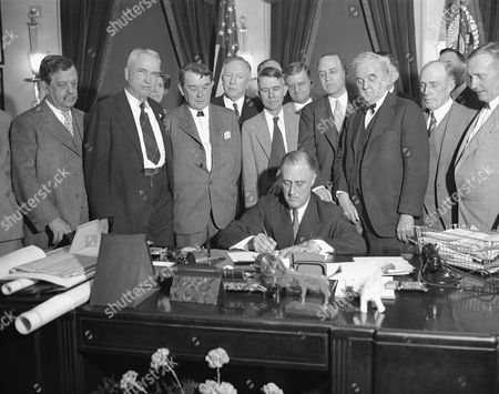 President Franklin D. Roosevelt signs the Norris-Hill Bill to develop the Tennessee Valley, . From left: Sen. Ellison D. Smith of South Carolina; Rep. John J. McSwain of South Carolina; Sen. Kenneth D. McKellar of Tennessee; Rep. Samuel Davis McReynolds of Tennessee; Reps. Miles C. Allgood, William Bacon Oliver and Lister Hill, all of Alabama; Sen. George William Norris of Nebraska; and looking over his shoulder is Rep. Edward B. Almon, whose district is Muscle Shoals