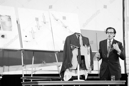 Dr. Michael Baden, New York City's chief medical examiner, appearing before the House Assassinations Committee in Washington, shows the coat that President John F. Kennedy wore the day he was assassinated in Dallas, Texas