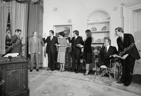 Stock Photo of President Jimmy Carter looks on as three new appointees are sworn in at the White House in Washington, . From left are Carter; Evan S. Dobelle, new chief of protocol, and his wife Kit; Sam Brown, new director of ACTION, and Alison Teal holding Bible; and Max Cleland, new veterans affairs administrator and Rev. George Watson holding Bible