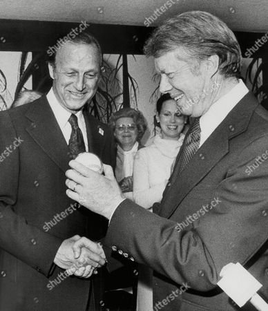 Jimmy Carter holds a baseball presented to him by Stan ?The Man? Musial during a campaign stop in St. Louis on . Carter spent the night at a hotel owned by Musial and was scheduled to resume his last-minute campaign swing on Saturday. Carter appeared at a rally at a suburban shopping center on Friday. His visit came only hours after President Ford held a rally at a park in downtown St. Louis