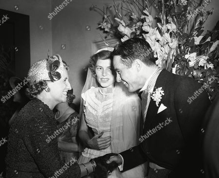 Margaret Truman, daughter of former president Harry S. Truman, congratulates newlyweds, Robert Sargent Shriver, Jr. and Eunice Kennedy Shriver, at their wedding reception, at the Waldorf-Astoria in New York