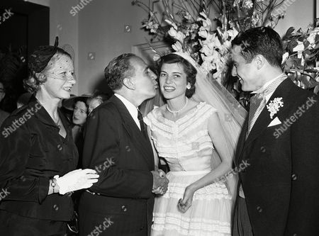 New York's Mayor Vincent R. Impellitteri puckers up to plant kiss on cheek of Mrs. Robert Sargent Shriver, Jr., the former Miss Eunice Kennedy at their wedding reception, at the Waldorf-Astoria in New York. At left is Elizabeth Agnes Impellitteri and at right is the bridegroom. Wedding and reception was one of the highlights of the current social season in New York