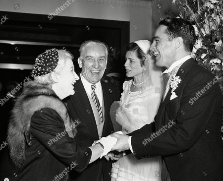 Judge William Touhey and Mrs. Touhey of Chicago, congratulate Mr. and Mrs. Robert Sargent Shriver, Jr. at wedding reception at the Waldorf-Astoria in New York, . The bride, the former Eunice Kennedy, is a daughter of Joseph P. Kennedy, former U.S. Ambassador to Great Britain. Wedding and reception highlighted the New York social season
