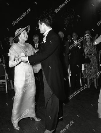 Robert Sargent Shriver, Jr., of Chicago, dances with Rose Kennedy, his new mother-in-law, at reception, in Waldorf Astoria Hotel in New York, following wedding ceremony for Shriver and his bride, the former Eunice Mary Kennedy at St. Patrick's Cathedral. The bride's father is Joseph P. Kennedy, former U.S. Ambassador to the Court of St. James's
