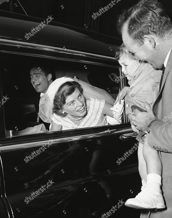 Eunice Kennedy Shriver., and her brand new husband Robert Sargent Shriver, Jr., smile from the car as they leave St. Patrick's Cathedral in New York, . Little Richard Snyder, 2, is held by his father, Aaron, as he greets the bride. The bride is a daughter of Mr. and Mrs. Joseph P. Kennedy, former U.S. Ambassador to the Court of St. James's