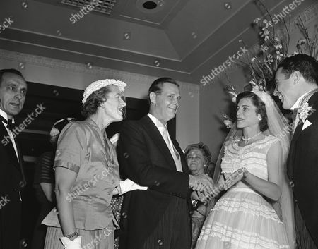 Maurice J. Tobin, and his wife Helen, left, congratulate Eunice Kennedy Shriver, and her brand new husband Robert Sargent Shriver, Jr., right, on their marriage, in New York. The bride is the daughter of Rose and Joseph P. Kennedy, former U.S. Ambassador to the Court of St. James 's. Tobin is former U.S. Secretary of Labor, and former governor of Massachusetts