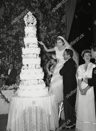 Robert Sargent Shriver, Jr., a brand new husband, helps his bride Eunice Kennedy Shriver, as she stands on a chair to cut multi-tiered wedding cake at their reception at Waldorf-Astoria in New York, . Bride is the daughter of Rose and Joseph P. Kennedy, of Palm Beach, Fla., and Hyannisport, Mass. The couple's wedding and reception was one of the highlights of the New York social season