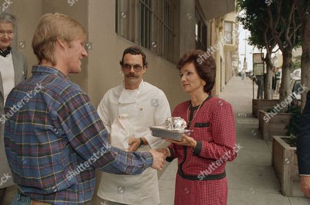 Stock Image of Kitty Dukakis Kitty Dukakis, wife of democratic presidential candidate Michael Dukakis, shakes the hand and delivers lunch to Timothy Keeton (left), a 29-year-old accountant with AIDS, outside his home in San Francisco, . Looking on is chef Chris Medina of the volunteer group project open hand. Mrs. Dukakis earlier in the day met with doctors and experts on AIDS