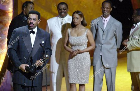 Stock Photo of CEDRIC Comic Steve Harvey accepts the award for Entertainer of the Year at the 32nd annual NAACP Image Awards, Saturday, March 3. 2001, in Los Angeles. Harvey's wife, Mary Harvey, looks on with comedians Arsenio Hall, rear left, J. Anthony Brown, Rickey Smiley, and Cedric the Entertainer, right