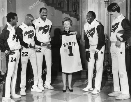 "First Lady Nancy Reagan receives a basketball jersey presented to her from the newly formed Shooting Stars basketball team during a ceremony in the Grand Foyer, at the White House. The stars are acting as ambassadors of the president's drug awareness campaign. From left, are: Larry Rivers, Frederic ""Curly"" Neal, Jerry Venable, Mrs. Reagan, Meadowlark Lemon and ""Pistol"" Pete Maravich"