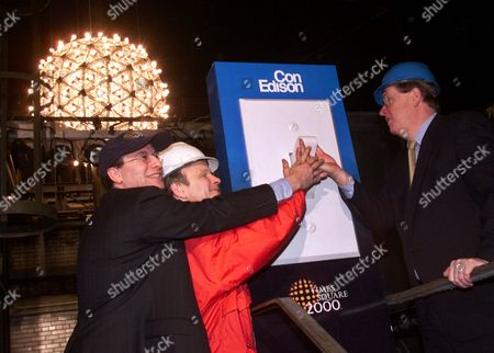 STRAUS SEXTON MCGRATH Jeffrey Straus, left, president of Countdown Entertainment, and Brendan Sexton, center, president of the Times Square Business Improvement District, and Con Edison Chairman Eugene McGrath, push the switch to light the Times Square ball in New York, Friday morning, as millennium festivities begin