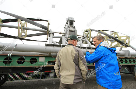Doug Johnson, right, director of development for Ocean Renewable Power Co., answers questions about the company's river turbine generator, in Anchorage, Alaska. In July, the company will install the device at the bottom of the Kvichak River at the village of Igiugig, Alaska, to test its usefulness for generating power in villages off the state power grid