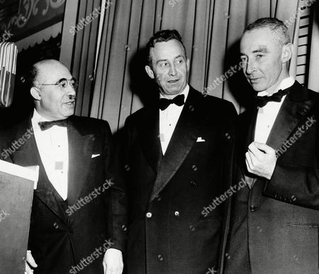 """Dr. J. Robert Oppenheimer, right, head of Princeton University's Institute for Advance Science, who earlier this year was denied security clearance by the Atomic Energy Commission and removed from all government work on the hydrogen bombs, chats with Dr. Howard Stratton, left, president of the Pyramid Club, and Professor Milton Stanley Livingston, President of the federation of American Scientists, at a dinner of the Pyramid Club in Philadelphia . Oppenheimer, whose clearance was denied on grounds he had associated with individuals of questionable loyalty to the United States, recieved the Club's award for achievement """"for unstinting devotion... his own great gifts to the end of increasing man's knowledge."""" Oppenheimer said the award reaffirms """"That spirit of human brother hood that is the hope of today's world"""