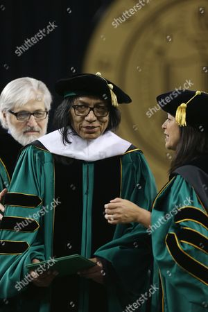 """Sixto Rodriguez Musician Sixto Rodriguez, center, is helped by Wayne State University Board of Governors Paul Massaron, left, and Sandra Hughes O'Brien, right, during the university's commencement ceremony in Detroit, . Rodriguez received a Doctor of Humane Letters honorary degree. Rodriguez's two albums in the early 1970s received little attention in the United States but he unknowingly developed a cult following in South Africa during the apartheid era. He was the subject of an Oscar-winning documentary, """"Searching for Sugar Man"""