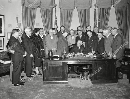 President Harry Truman signs the Upper Colorado River compact, in Washington. Watching from left to right: Rep. Frank Barret (R-Wyo.); Rep. William Hill (R-Colo.); Sen. Eugene Millikin (R-Colo.); Sen. Arthur Watkins (R-Utah); Mike Straus, Interior Dept.; Rep. Reva Bosone (R-Utah); Rep. Antonio Fernandez (D-N.M.), A.B. See., (CQ), secretary to Rep. Harold Patten (D-Ariz.); Sen. Elbert Thomas (D-Utah); Rep. John Miles (D-N.M.); Rep. Harold Patten (D-Ariz.); Interior Secretary Julius Krug; Sen. Joseph O'Mahoney (D-Wyo.); Sen. Lester Hunt (D-Wyo.): Sen. Dennis Chavez (D-N.M.); Sen. Clinton P. Anderson (D-N.M.); Rep. Wayne Aspinall (D-Colo.); Sen. Edwin Johnson (D-Colo.); Rep. John Murdock (D-Ariz.); Rep. John Marsalis (D-Colo.), Rep. J. Hardin Peterson (D-Fla.) (behind Marsalis); Sen. Ernest McFarland (D-Ariz.); Rep. Richard Welch (R-Calif.); and Rep. Walter Granger (D-Utah