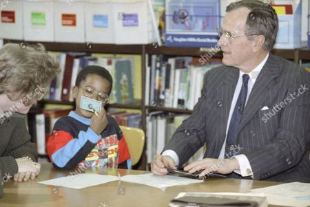 """Anthony Henderson U.S. President George H. Bush is asked if he is really the president by Anthony Henderson, 8, a third grade student at the Henderson Hall/Barcroft Elementary School in Arlington, Va., . The President reached in his wallet and pulled out his credit card to show the young man. Bush named volunteers at the school as the 400th """"Daily Point of Light"""