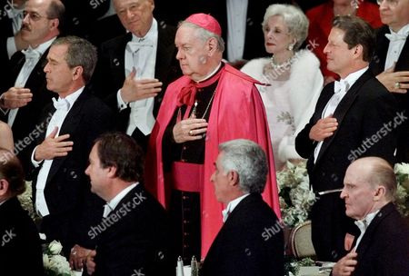 Stock Image of BUSH GORE EGAN New York Archbishop Edward Egan, center, stands between Republican presidential candidate Texas Gov. George W. Bush, left, and Democratic presidential candidate Vice President Al Gore, during the national anthem at the start of the Alfred E. Smith Memorial Foundation Dinner, in New York City. Egan is the leading US candidate expected to be named Cardinal next year