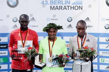 From left, second placed Wilson Kipsang of Kenya, winner Kenenisa Bekele of Ethiopia and third placed Evans Chebet of Kenya pose for media during the winners ceremony of the 43rd Berlin Marathon in Berlin, Germany