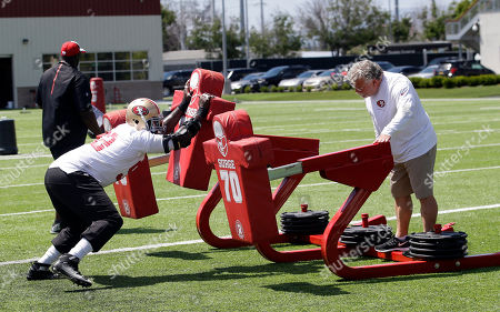 Jerry Azzinaro, Quinton Dial San Francisco 49ers defensive line coach Jerry Azzinaro, right, goes through drills with Quinton Dial during an NFL football practice, in Santa Clara, Calif
