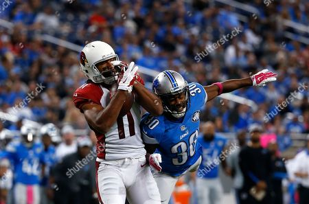 Arizona Cardinals wide receiver Larry Fitzgerald (11) pulls in a pass as Detroit Lions defensive back Josh Wilson (30) defends during the second half of an NFL football game, in Detroit