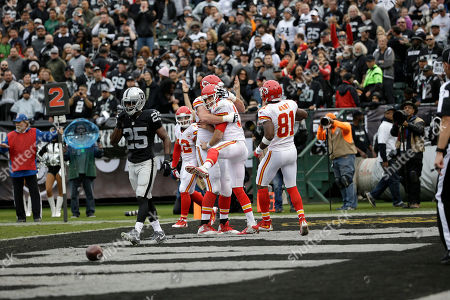 Alex Smith, Eric Fisher, Jason Avant Kansas City Chiefs quarterback Alex Smith, center, celebrates with offensive tackle Eric Fisher and wide receiver Jason Avant (81) after running for a touchdown against the Oakland Raiders during the first half of an NFL football game in Oakland, Calif