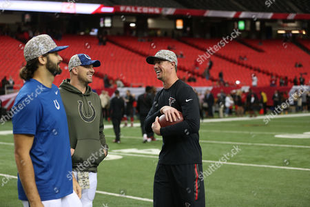 Atlanta Falcons quarterback Matt Ryan, right, Indianapolis Colts quarterback Matt Hasselbeck, center, and Indianapolis Colts quarterback Charlie Whitehurst, speak while wearing Salute to Service caps before the first of an NFL football game between the Atlanta Falcons and the Indianapolis Colts, in Atlanta