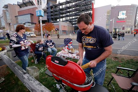 Brian Williams, right, tends the grill while tailgating with his wife Kris Williams, left, Katie Jones, second from left, and Jason Spangenberg, third from left, all of Erie, Pa., in the parking lot of Gillette Stadium before an NFL football game between the New England Patriots and Miami Dolphins, in Foxborough, Mass