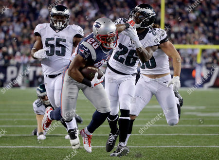 James White, Brandon Graham, Walter Thurmond New England Patriots running back James White (28) runs from Philadelphia Eagles linebacker Brandon Graham (55) as he stiff-arms Eagles safety Walter Thurmond (26) during the second half of an NFL football game, in Foxborough, Mass