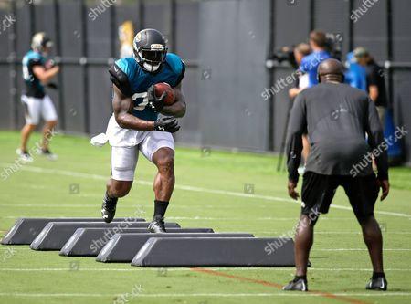 Jacksonville Jaguars running back Jonas Gray, left, performs a drill during NFL football training camp, in Jacksonville, Fla