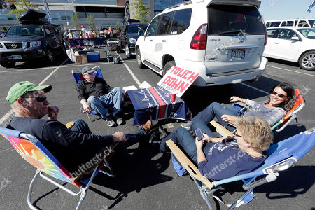 Clockwise from front left, Bill Powers, Jean Lyons, Beth Powers and Dave Lyons spend time tailgating in the parking lot of Gillette Stadium before an NFL football game between the New England Patriots and Jacksonville Jaguars, in Foxborough, Mass