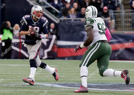 Stock Image of Muhammad Wilkerson, Tom Brady New England Patriots quarterback Tom Brady (12) scrambles away from New York Jets defensive end Muhammad Wilkerson (96) during the second half of an NFL football game, in Foxborough, Mass