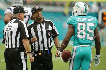 Greg Jennings, Rusty Baynes, Adrian Hill Miami Dolphins wide receiver Greg Jennings (85) waits for a decision by line judge Rusty Baynes (59) and field judge Adrian Hill (29) during the second half of an NFL football game against the New England Patriots, in Miami Gardens, Fla