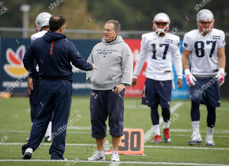 Mike Lombardi, Bill Belichick, Aaron Dobson, Rob Gronkowski New England Patriots assistant to the coaching staff Mike Lombardi, left, speaks with head coach Bill Belichick, right, during an NFL football practice, in Foxborough, Mass. Patriots wide receiver Aaron Dobson (17) and tight end Rob Gronkowski (87), walk on the field at right