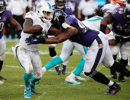 Chris Canty, Lamar Miller Baltimore Ravens defensive end Chris Canty (99) attempts to tackle Miami Dolphins running back Lamar Miller (26) during the second half of an NFL football game, in Miami Gardens, Fla