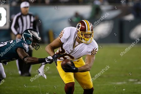 Washington Redskins' Jordan Reed, right, tries to break a tackle by Philadelphia Eagles' Walter Thurmond in the second half of an NFL football game, in Philadelphia