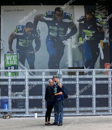 "Matt McHugo, Sydney Proback Matt McHugo, right, and Sydney Probach, left, both of Auburn, Wash., pose for a ""selfie"" photo at CenturyLink Field in front of a photo of Seattle Seahawks' (from left) Earl Thomas, Kam Chancellor, and Richard Sherman, as they wait to buy single-game Seahawks NFL football tickets in Seattle. The couple spent more than nine hours in line on Sunday to get wristbands securing their places in line Monday when ticket sales began"