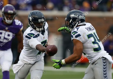 Stock Image of Tarvaris Jackson Seattle Seahawks quarterback Tarvaris Jackson (7) hands off to running back Thomas Rawls (34) against the Minnesota Vikings in the second half of an NFL football game in Minneapolis