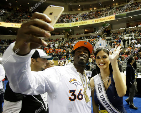 Miss Universe Pia Alonzo Wurtzbach poses with Denver Broncos cornerback Kayvon Webster during Opening Night for the NFL Super Bowl 50 football game, in San Jose, Calif
