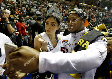 Miss Universe Pia Alonzo Wurtzbach poses for a cell phone photos with Denver Broncos outside linebacker Corey Nelson during Opening Night for the NFL Super Bowl 50 football game, in San Jose, Calif
