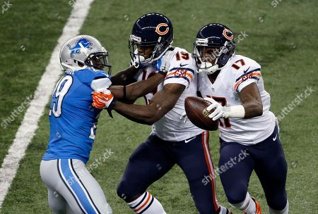 Alshon Jeffery, Josh Morgan, Cassius Vaughn Chicago Bears wide receiver Alshon Jeffery (17) runs with the ball in one hand after a catch as wide receiver Josh Morgan (19) blocks Detroit Lions cornerback Cassius Vaughn (29) during an NFL football game in Detroit