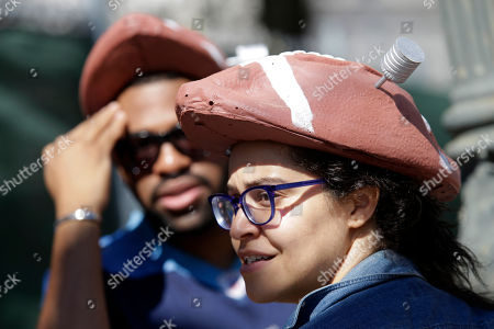 Stock Photo of Christopher Russell, of Brooklyn, N.Y., and Enid Peralta, of Queens, N.Y., wear deflated football hats outside federal court, in New York. New England Patriots quarterback Tom Brady and NFL Commissioner Roger Goodell are set to explain to a judge why a controversy over underinflated footballs at last season's AFC conference championship game is spilling into a new season