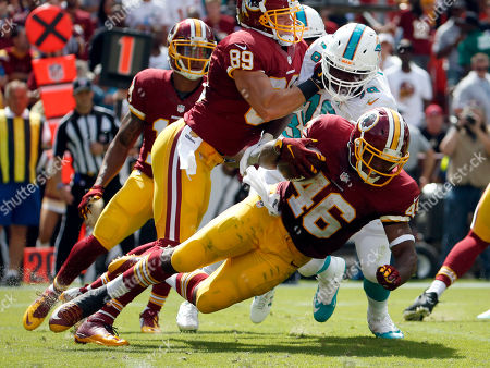 Alfred Morris, Terrence Fede, Derek Carrier Washington Redskins running back Alfred Morris (46) tries to get away from Miami Dolphins defensive end Terrence Fede (78) who is blocked by Redskins tight end Derek Carrier (89) during the first half of an NFL football game, in Landover, Md