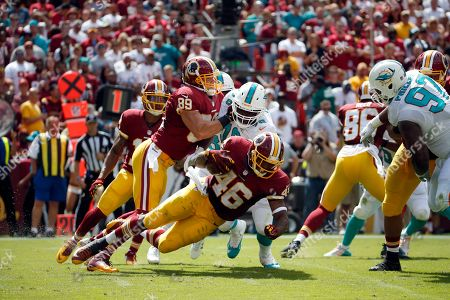 Alfred Morris, Terrence Fede, Derek Carrier Washington Redskins running back Alfred Morris (46) tries to get away from Miami Dolphins defensive end Terrence Fede (78) as he is blocked by tight end Derek Carrier (89) during the first half of an NFL football game, in Landover, Md
