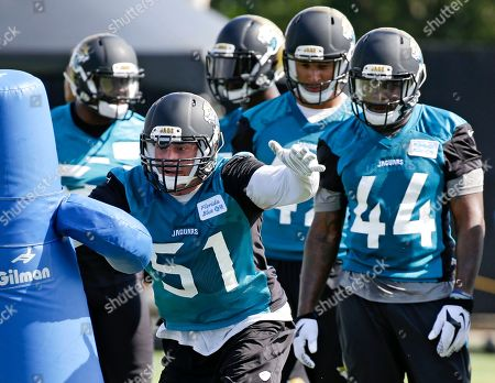 Jacksonville Jaguars middle linebacker Paul Posluszny (51) goes through a drill as teammates, including linebacker Todd Thomas (44) look on during practice at NFL football training camp, in Jacksonville, Fla