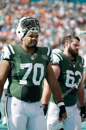Dakota Dozier, Dalton Freeman New York Jets tackle Dakota Dozier (70) and center Dalton Freeman (63) walk the sidelines during the first half of an NFL football game against the Miami Dolphins, in Miami Gardens, Fla