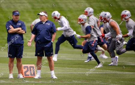 Stock Photo of Michale Lombardi New England Patriots head coach Bill Belichick, second from left, talks with Michael Lombardi, an assistant to the coaching staff, during an NFL football minicamp, in Foxborough, Mass