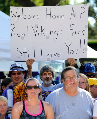 Stock Picture of Minnesota Vikings' fan Barry Jones, center, from St. Paul., Minn., hold up a sign welcoming back running back Adrian Peterson as the Vikings report to an NFL football training camp, in Mankato, Minn